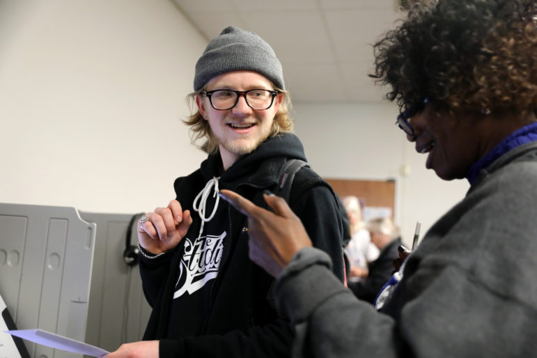 Asher Bernick-Roehr, a freshman at University of Wisconsin-Madison from St. Paul, Minn., casts his ballot during early voting on March 13, 2020, at the City Clerk's office in Madison, Wis. He is assisted by absentee ballot clerk Teresa Holmes. College students in Wisconsin have additional requirements for voting that other voters do not face. Photo by Coburn Dukehart / Wisconsin Watch.