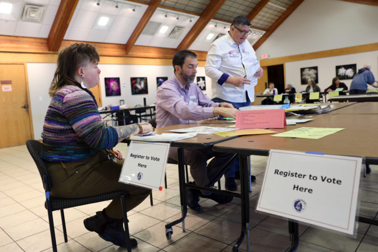 Alix Yarrow, left, registers to vote at the polling place at Olbrich Botanical Gardens in Madison, Wis., on Feb. 18. Yarrow had recently changed addresses within the city. Assisting in the registration process are Kyle Richmond, center, and Aaron Schultz, right. Wisconsin voters on the list for possible deactivation because they have moved can change their addresses at the polls on Election Day. Photo by Coburn Dukehart / Wisconsin Watch.