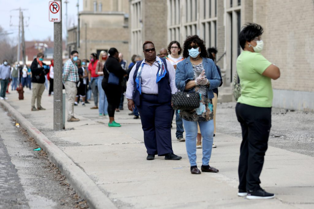 Voters waited for hours in long lines to vote in Milwaukee on April 7, 2020. Here, the voting line wraps around the block outside Washington High School. Researchers say that consolidating polling sites and health concerns of voting in-person during the pandemic kept many Milwaukee voters away, especially Black residents. Photo by Coburn Dukehart/Wisconsin Watch.