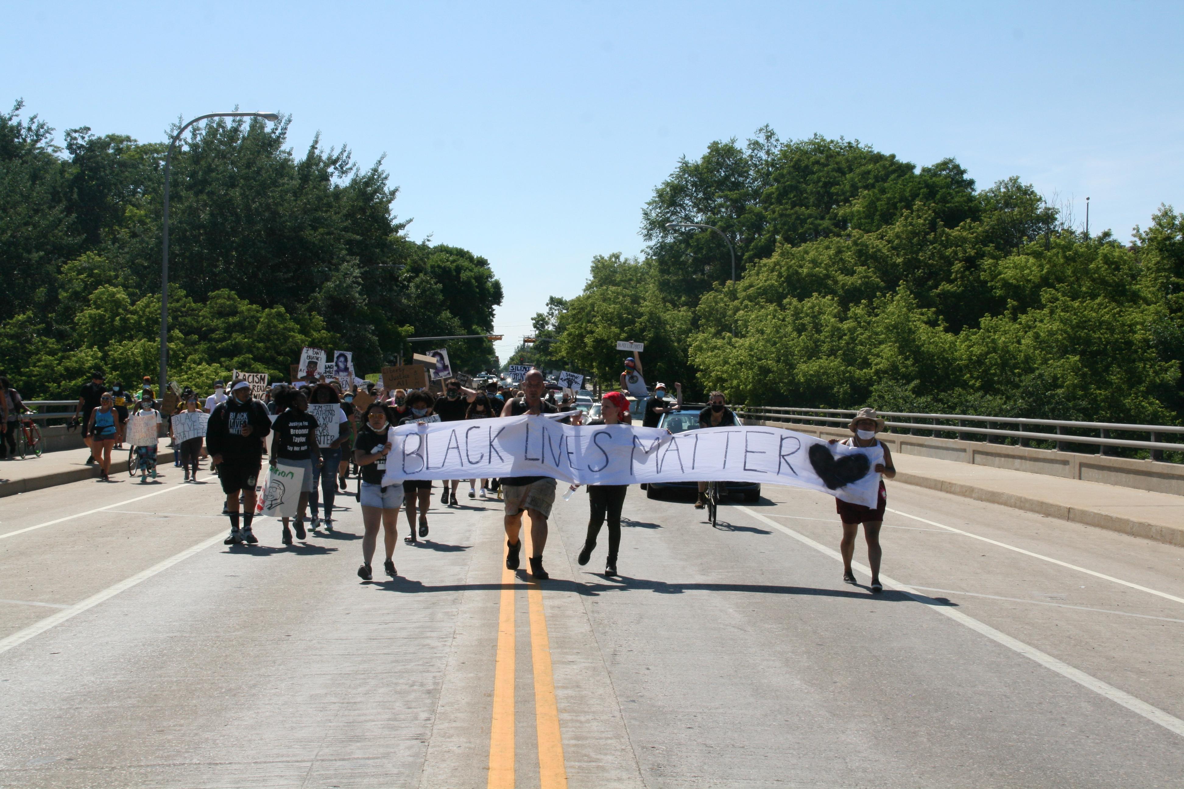 Black Lives Matter sign held by marchers crossing Locust Street bridge. Photo by Jeramey Jannene.