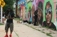 Frank Nitty hosts a Facebook live video while artist Chris Burke restores a portrait of Nitty that was vandalized. Photo by Jeramey Jannene.