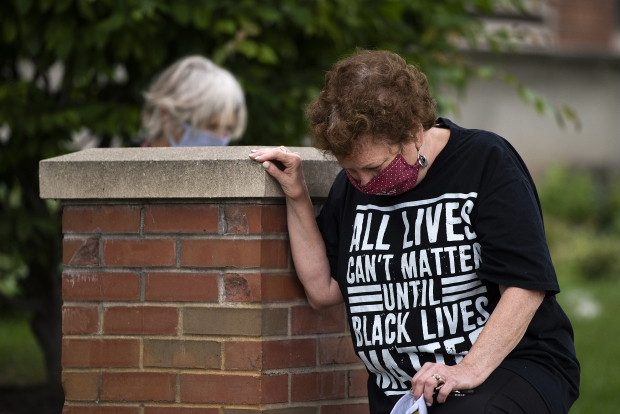 Tracy Suprise, a retired nurse from Madison, kneels in solidarity during the Strike for Black Lives on Monday, July 20, 2020, in Madison. Angela Major/WPR