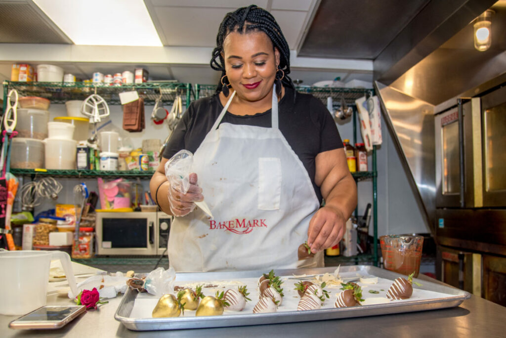 Adija Greer-Smith prepares chocolate-covered strawberries in the kitchen of her Milwaukee bakery, Confectionately Yours, on July 2, 2020. Photo courtesy of NNS.