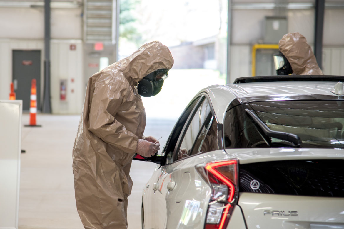 Public Health Madison and Dane County employees and members of the Wisconsin National Guard operate a drive-through testing facility for COVID-19 at the Alliant Energy Center in Madison, Wis., on May 13, 2020. Tracing the contacts of people who test positive is considered an important way to curb the pandemic. But online conspiracy theories about contact tracing have generated suspicion and mistrust. Photo by Will Cioci/Wisconsin Watch.