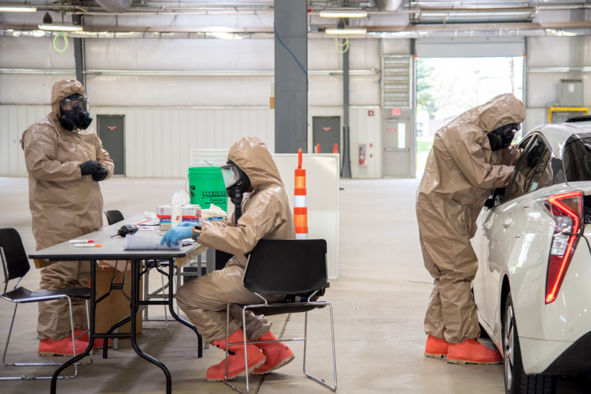 Public Health Madison and Dane County employees and members of the Wisconsin National Guard operate a drive-through COVID-19 testing facility at the Alliant Energy Center in Madison, Wis., on May 13, 2020. Here, Wisconsin National Guard members perform the tests, asking people to blow their noses before administering nasal swabs. Wisconsin has dramatically expanded its testing capacity during the pandemic, but experts say too few Wisconsinites are showing up — potentially thwarting efforts to neutralize the virus. Photo by Will Cioci/Wisconsin Watch.