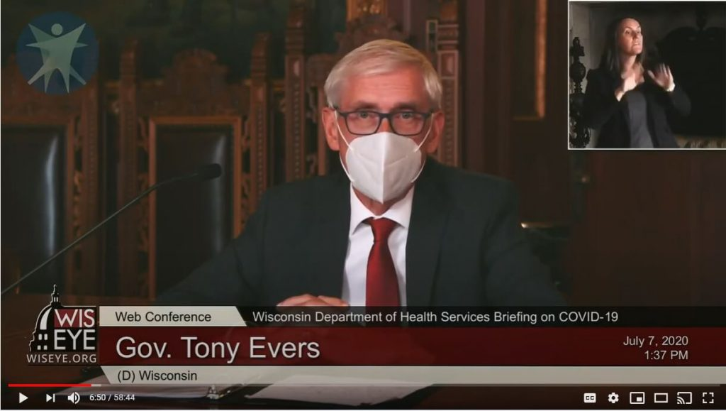 Wearing a protective mask as recommended by public health experts to reduce the spread of COVID-19, Gov. Tony Evers addresses reporters in a telephone and live-streamed news conference Thuesday, July 7. (Screenshot from Youtube)