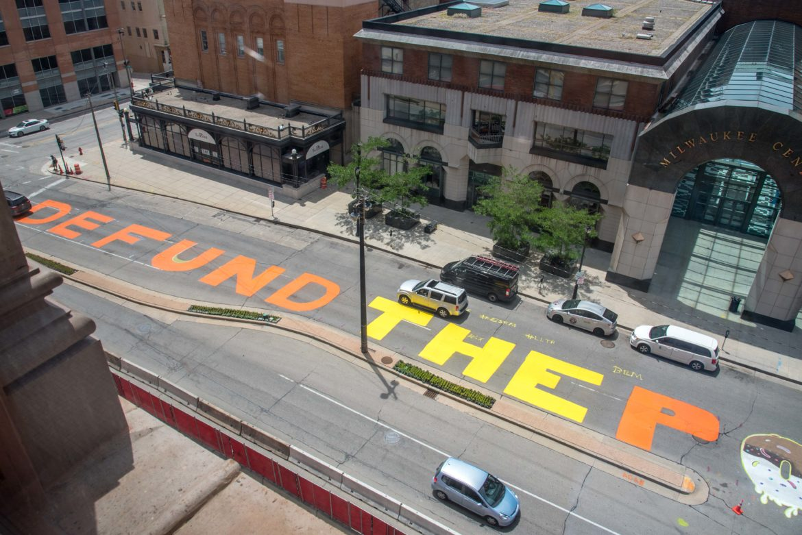 """Defund the police"" is seen painted across a block of North Water Street in Milwaukee on July 2, 2020. The Milwaukee Department of Public Works removed the paint a week later, saying it presented ""serious traffic safety concerns"" because it covered traffic markings and was slick when wet. ""The message painted on Water Street has been heard loud and clear by policy makers in city government, and the Department of Public Works has no intention to diminish the voices calling for change,"" Commissioner of Public Works Jeff Polenske said in a July 9 statement. ""Our concern for unauthorized street art including the current mural on Water Street is solely about safety."" Will Cioci/Wisconsin Watch."