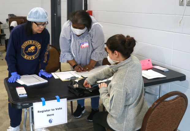 Poll workers help Alex Mendez, right, register to vote at Warner Park in Madison during Wisconsin's spring primary election on April 7, 2020. Steven Potter/WPR.