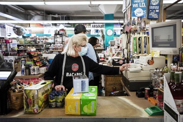 Judi Redding, an employee at Discount Liquor in Waukesha, checks out a customer Thursday, July 30, 2020. Angela Major/WPR