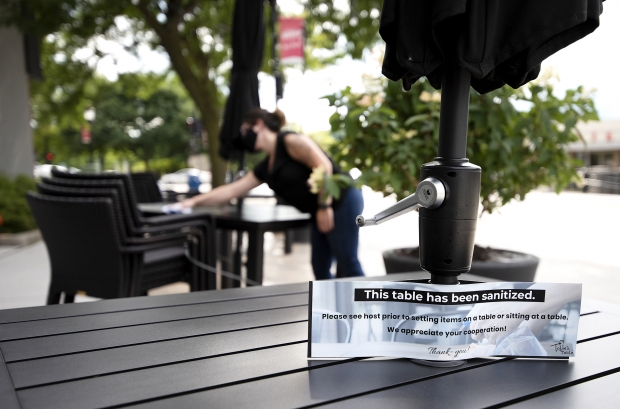 Workers at Tofte's Table clean outdoor tables for customers Friday, Jul 31, 2020, in Waukesha. Angela Major/WPR