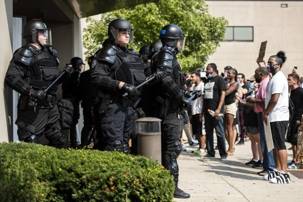 Police emerge from the Kenosha County Public Safety Building to confront protesters after some tried to gain access to a press conference and damaged a door to the building Monday, Aug. 24, 2020, in Kenosha. Angela Major/WPR