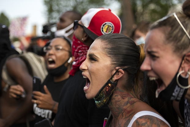 Shyne Marie of Milwaukee yells with the crowd facing police in riot gear Monday, Aug. 24, 2020, in Kenosha. Angela Major/WPR