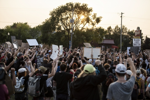 Protesters raise their fists in the air as they proceed form Civic Center Park on Monday, Aug. 24, 2020, in Kenosha. Angela Major/WPR