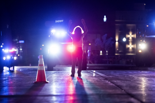 A protester stands in front of bearcats as people are cleared out of the area Wednesday, Aug. 26, 2020, in Kenosha. Angela Major/WPR