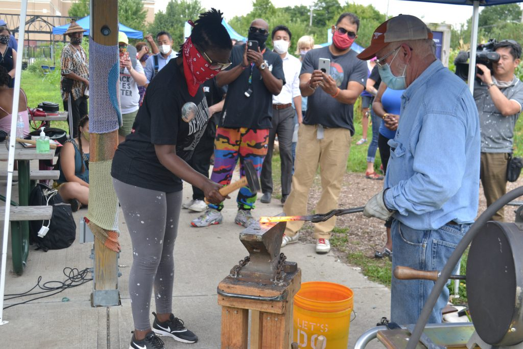 Camille Mays hammers on a piece of a gun barrel being remade into a garden tool, as Fred Martin holds it with tongs on a blacksmithing anvil. Photo by Erik Gunn/Wisconsin Examiner.