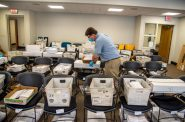 Election official Jim Fortner places a crate of sorted absentee ballots with others from the same ward at the Madison, Wis., City-County Building on Aug. 5, 2020. Madison elections workers alphabetized each returned absentee ballot by hand in preparation for Wisconsin's partisan primary on Tuesday. Delays and failure to deliver absentee ballots in Wisconsin and other key swing states have sparked concerns about how well the November presidential election will be managed during the pandemic. Will Cioci/Wisconsin Watch