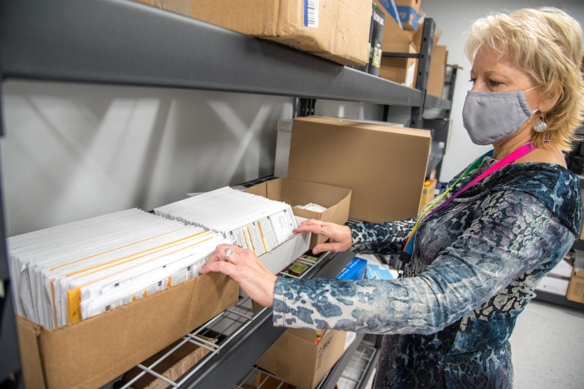 Barbara Goeckner, deputy clerk for the village of Cambridge, Wis., sorts through returned absentee ballots on Aug. 7, 2020. Goeckner says her office has seen an uptick in mail-in voting amid the COVID-19 pandemic. Goeckner serves on the U.S. Election Assistance Commission, an independent, bipartisan commission charged with developing guidance to meet Help America Vote Act requirements. Will Cioci
