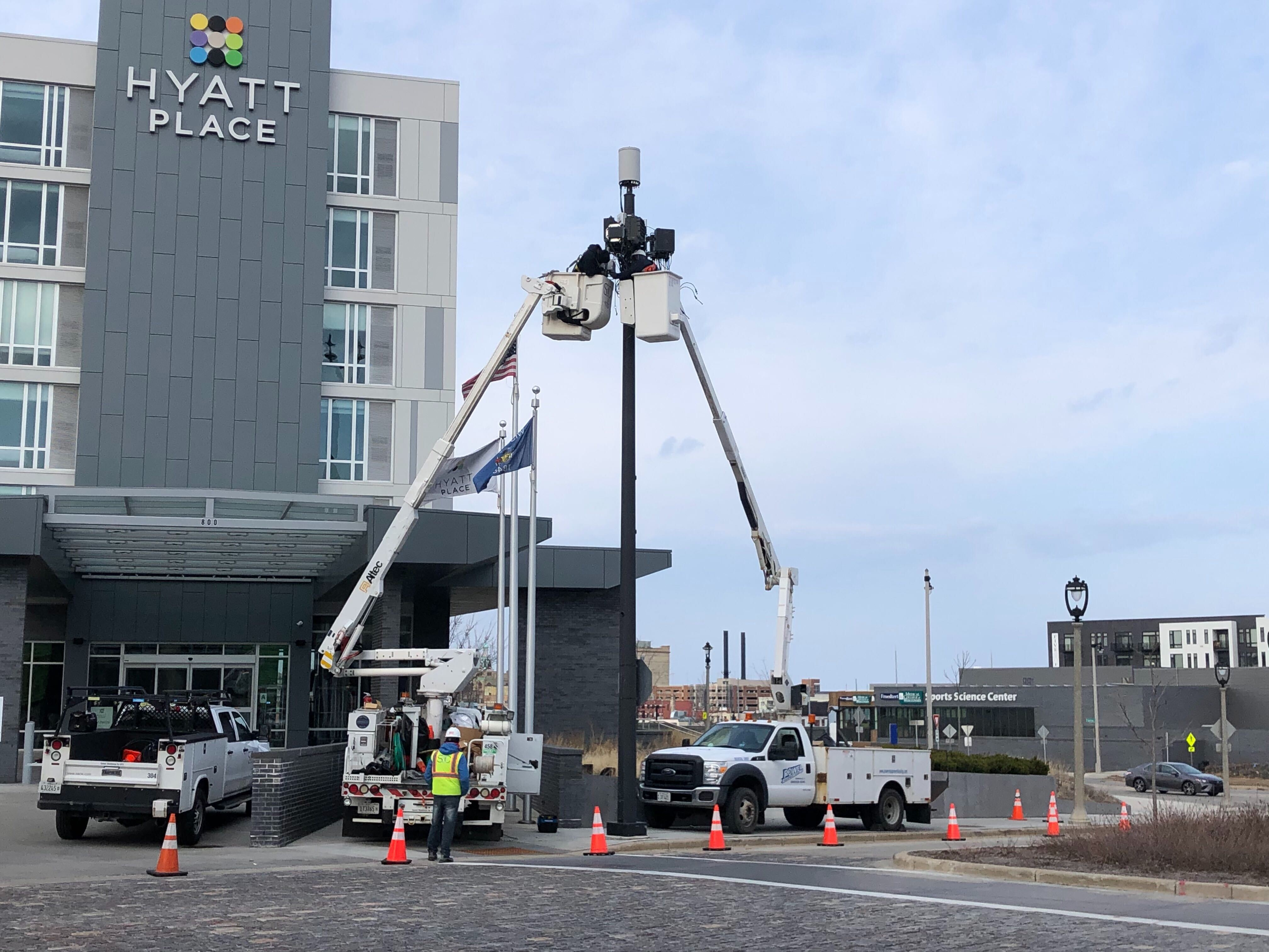 A crew installs 5G cellular equipment atop a utility pole in the Brewery District in April 2020. Photo by Jeramey Jannene.