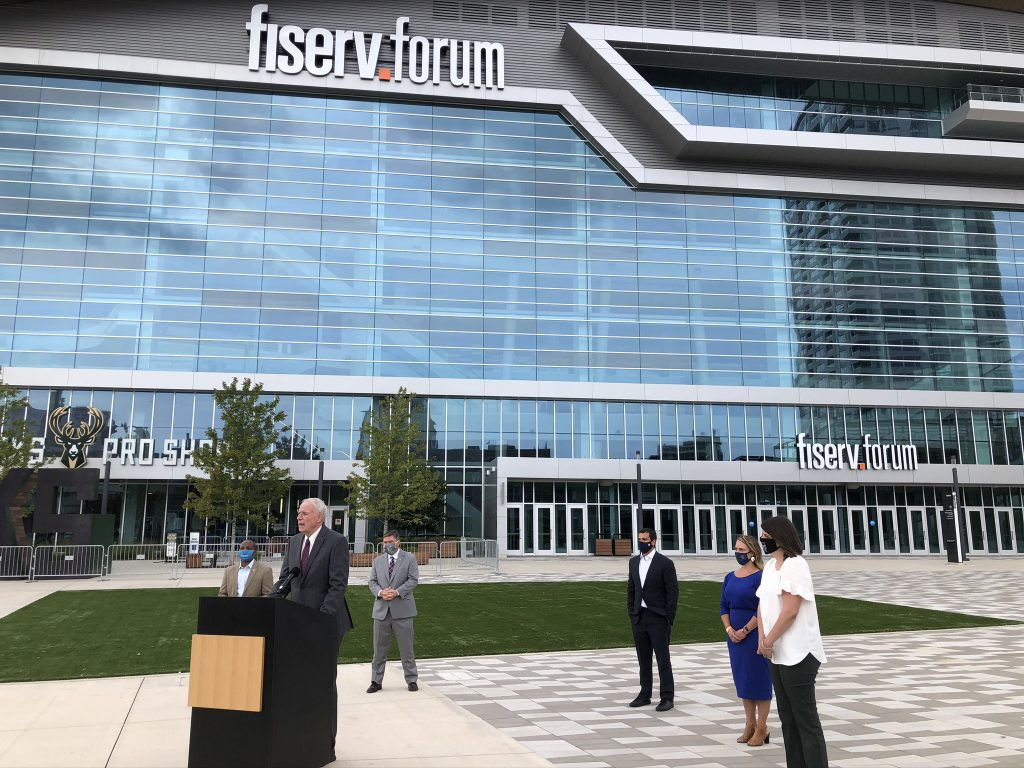 Mayor Tom Barrett speaks outside Fiserv Forum as council president Cavalier Johnson, county clerk George Christenson, Bucks vice president Alex Lasry, Brewers director Leslie Stachowiak and Milwaukee election commission director Claire Woodall-Vogg look on. Photo by Jeramey Jannene.