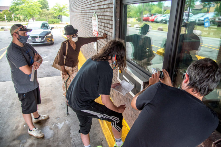 Members of the Milwaukee Autonomous Tenants Union and Rebecca Moore-Gnacinski, second from left, deliver a letter demanding that Berrada Properties, Moore-Gnacinski's landlord, end its attempt to evict her on August 10, 2020. Photo by Will Cioci / Wisconsin Watch.