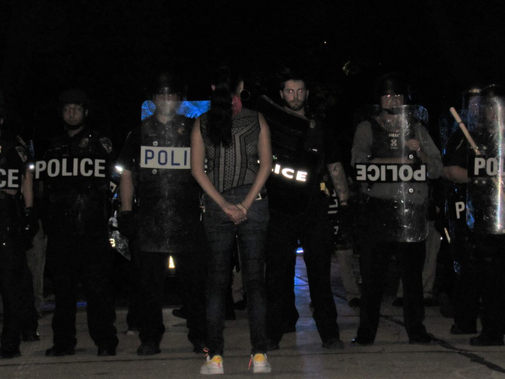 Kimberley Motley, one of the lawyers representing the families of those Officer Joseph Mensah has killed, confonts the numerous officers clad in riot gear in Wauwatosa the evening of August 14th, 2020. Photo by Isiah Holmes/Wisconsin Examiner.