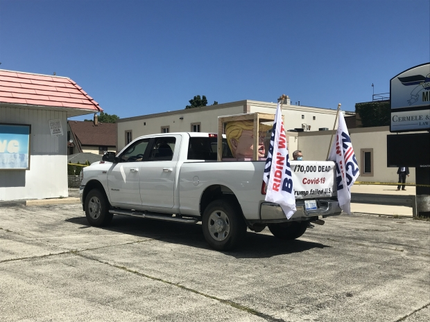 """Bruce Fealk and Tom Moran of Michigan rented a pickup truck to carry a papier-mache Trump head and """"Ridin' for Biden"""" flags to Trump campaign events around Wisconsin. The two men said they were distressed by the president's handling of the COVID-19 pandemic. Madeline Fox/WPR"""