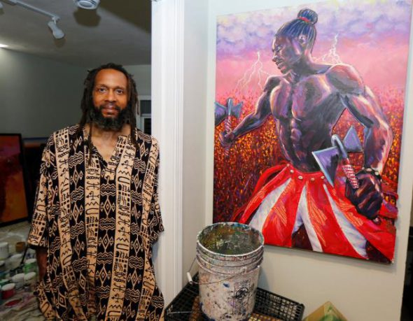 "Ras 'Ammar Nsoroma Photo By Pat Robinson. Pictured with his work entitled: ""Shango"", from The 7 African Powers Series, mixed media (acrylic paint & collage), 2011"