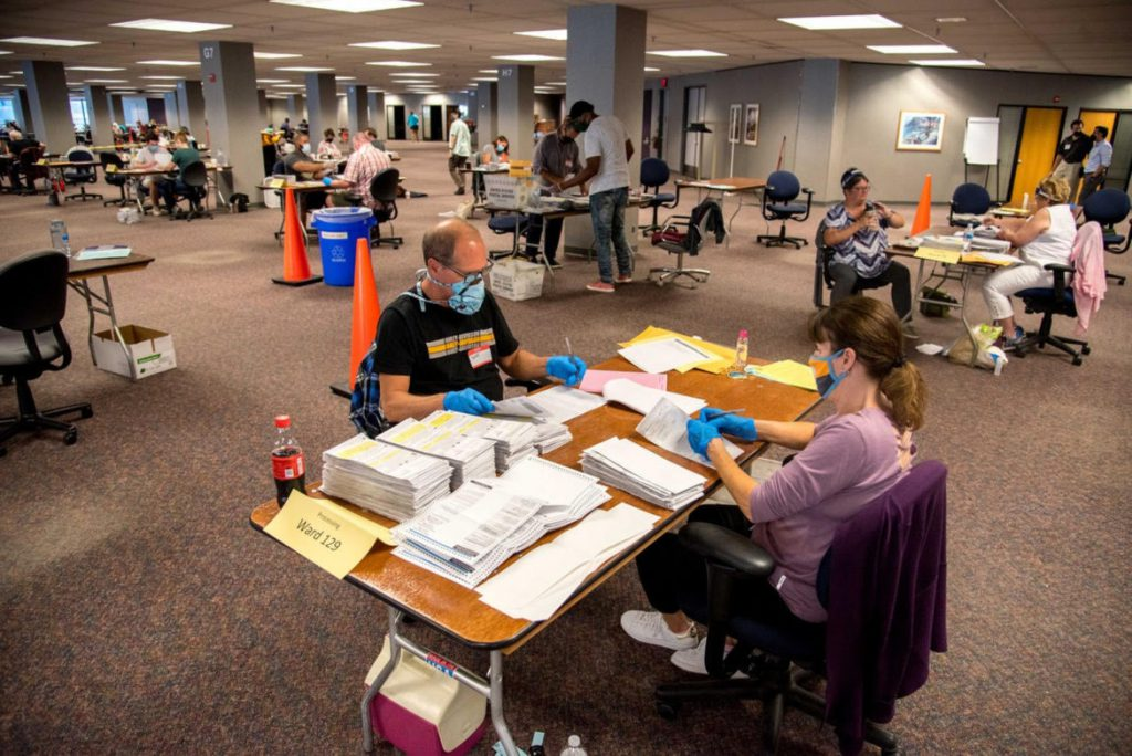 """Election workers Jeff and Lori Lutzka process absentee ballots at Milwaukee's """"central count"""" location on during Wisconsin's partisan primary election on Tuesday. Photo taken Aug. 11, 2020. Will Cioci / Wisconsin Watch"""