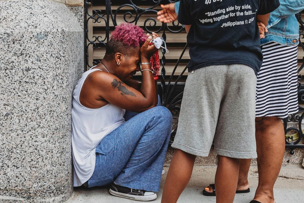 """""""In the days following my assault I was diagnosed with a concussion and I began having anxiety attacks."""" The author is seen here overcome by emotion at a recent protest. Photo provided by Azure Mahara/NNS."""
