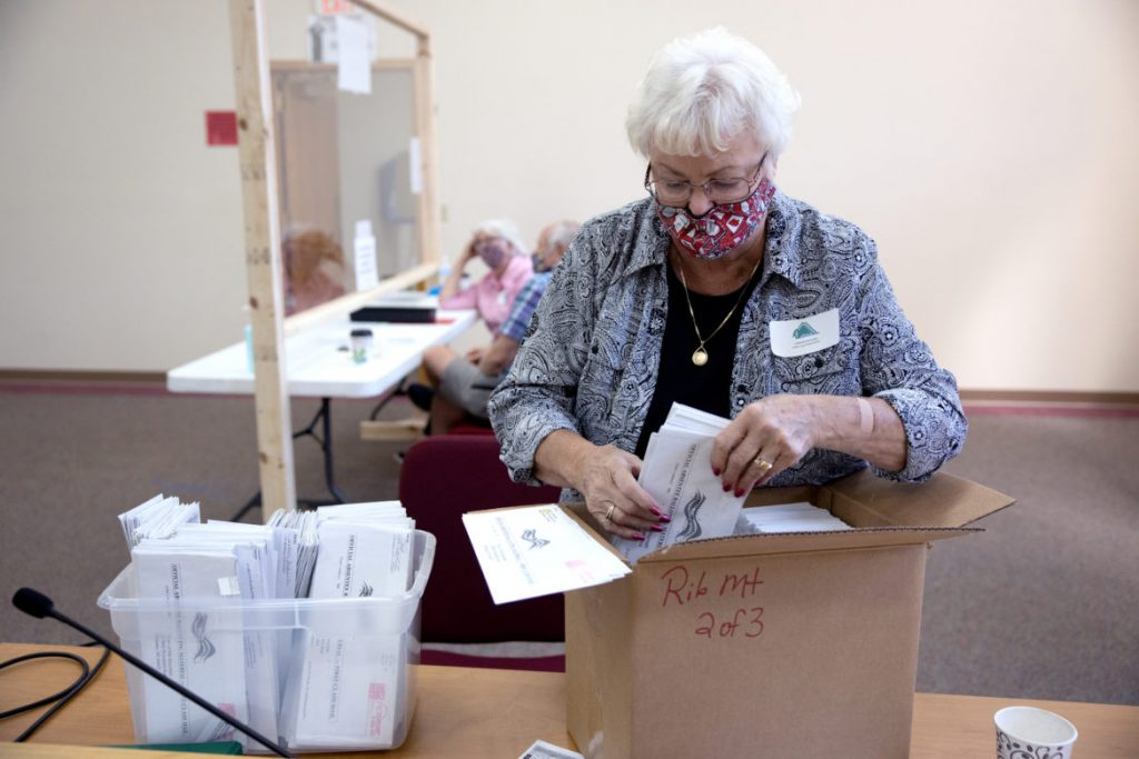 Sharon Drefcinski, chief election inspector for the town of Rib Mountain, Wis., boxes mailed-in absentee ballots to send to the county for archiving, during the partisan primary on Aug. 11, 2020. Town Clerk Joanne Ruechel sent out 1,348 absentee ballots ahead of Tuesday's election. Coburn Dukehart / Wisconsin Watch
