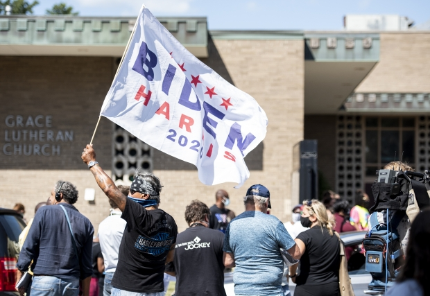 A man holds a Biden flag outside of a church where Democratic candidate Joe Biden was speaking Thursday, Sept. 3, 2020, in Kenosha. Angela Major/WPR
