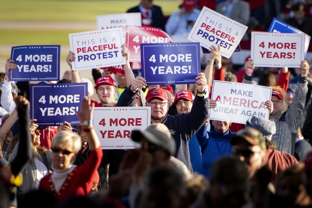 Supporters of President Donald Trump hold signs and cheer as television reporters go live from the risers Thursday, Sept. 17, 2020, in Mosinee, Wis. Angela Major/WPR