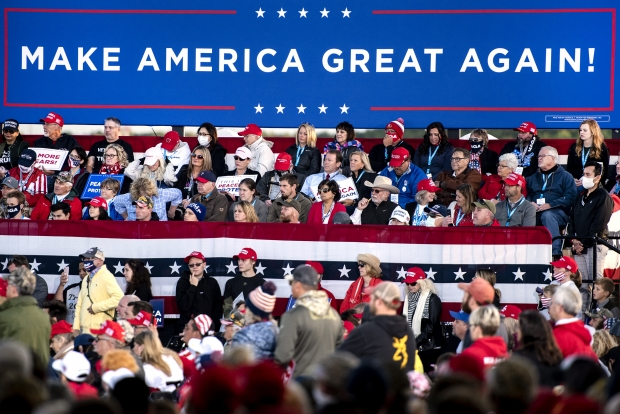 """A """"Make America Great Again"""" banner is set up behind rally attendees Thursday, Sept. 17, 2020, in Mosinee, Wis. Angela Major/WPR"""