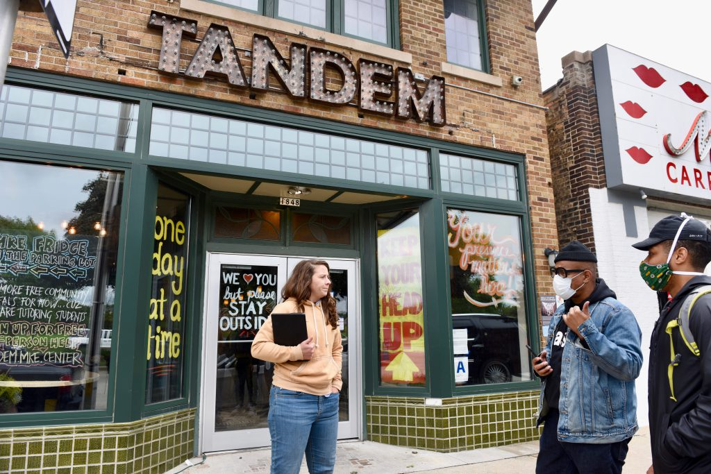Caitlin Cullen, owner of The Tandem, has opened an outdoor area for students to get Wi-Fi and tutoring help. Here she takes orders for the restaurant's free community meals program. Photo by Susan Vliet/NNS.