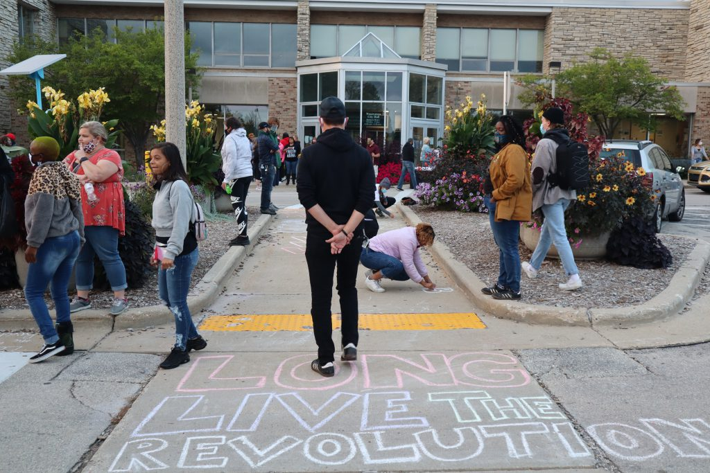 "Protesters with The People's Revolution stand outside Wauwatosa City Hall. The words ""long live the revolution"" was chalked on the ground. Photo by Isiah Holmes/Wisconsin Examiner."