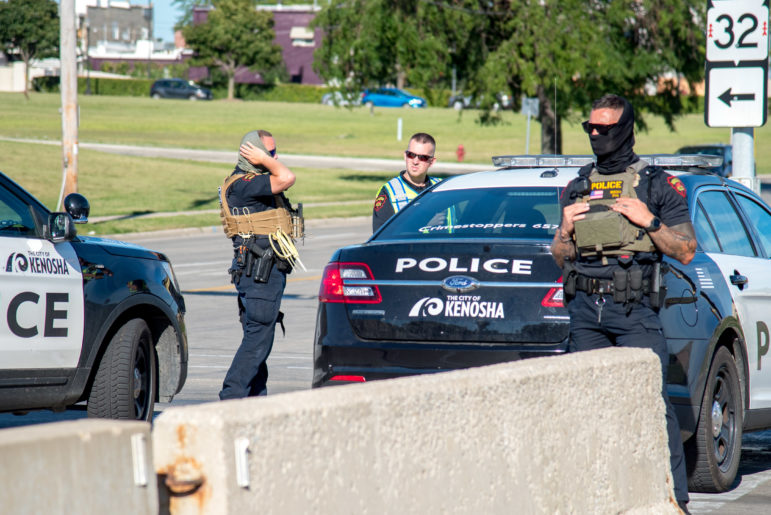 Kenosha, Wis., police officers are seen near the edge of a rally calling for justice for Jacob Blake, a Black man who was shot seven times by a Kenosha police officer. Photographed on Aug. 29, 2020. File photo by Will Cioci / Wisconsin Watch