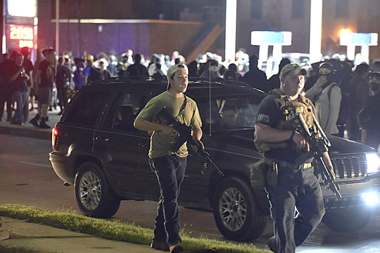"""Kyle Rittenhouse, left, with backwards cap, walks along Sheridan Road in Kenosha, Wis., on Aug. 25, 2020 with Ryan Balch, another militia member. Rittenhouse was charged in the fatal shooting of two protesters and the wounding of a third during a night of unrest in Kenosha following the police shooting of Jacob Blake. Balch claims police told him they planned to push protesters toward the armed civilians to allow the militia to """"deal with them."""" Kenosha police have not responded to that allegation. Adam Rogan / The Journal Times via AP."""