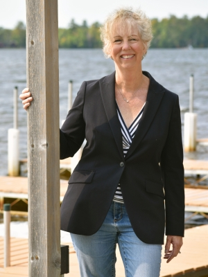 Kathy Schmitz, executive director of the Vilas County Economic Development Corp., stands on the dock by the Chippewa Retreat Resort on Manitowish Lake on Tuesday, Sept. 15, 2020. Schmitz said she's been getting calls regularly since March from people who are weighing a move to northern Wisconsin. Danielle Kaeding/WPR