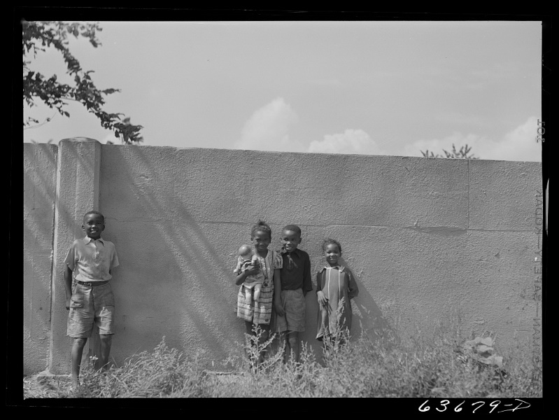 This wall in Detroit, Michigan was built in 1941 to separate an African-American neighborhood from a new housing development for white residents. Photo from the Library of Congress. (Public Domain).