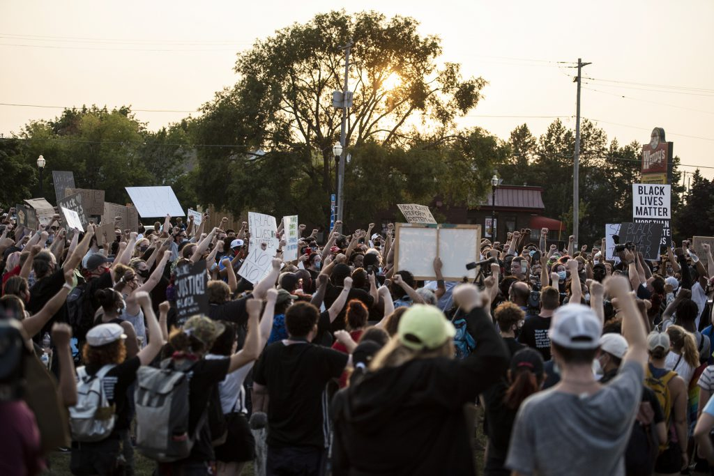 Protesters raise their fists in the air near Kenosha's Civic Center Park on Monday, Aug. 24, 2020. Angela Major/WPR