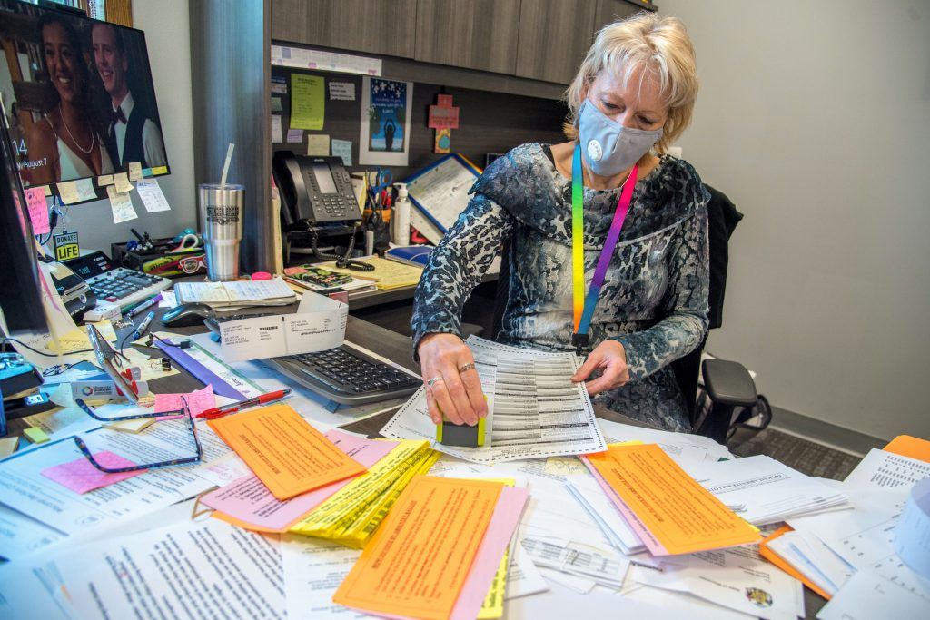 Deputy Clerk Barb Goeckner prepares outgoing absentee ballot envelopes for voters in Cambridge, Wis., on Aug. 7, 2020. Top U.S. security officials warn that foreign actors continue their efforts to tamper with the 2020 presidential election, although there is no evidence that voter registrations or vote totals have ever been altered. Will Cioci / Wisconsin Watch