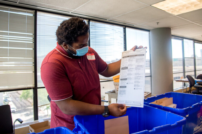 "Poll worker DeAngelo ""DJ"" Nash displays one of the blank absentee ballots at Milwaukee's central count facility on Aug. 11, 2020. The blank ballots are used when necessary to reconstruct absentee ballots that were damaged or not filled out properly. Will Cioci / Wisconsin Watch"