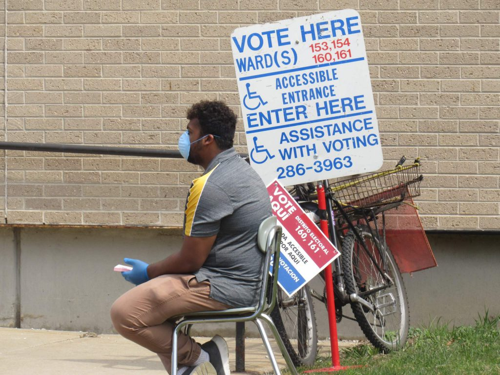 A poll worker sits outside of Washington High School wearing a protective mask. Photo by Isiah Holmes/Wisconsin Examiner.