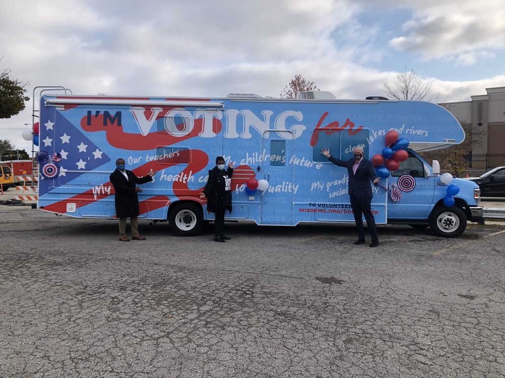 Cavalier Johnson, LaTonya Johnson and Tom Barrett stand in front of the Biden-Harris campaign bus. Photo by Jeramey Jannene.