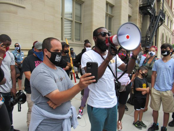 Rep. Jonathan Brostoff (left) stands beside Rep. David Bowen who is speaking to protesters through a megaphone. Photo by Isiah Holmes/Wisconsin Examiner.
