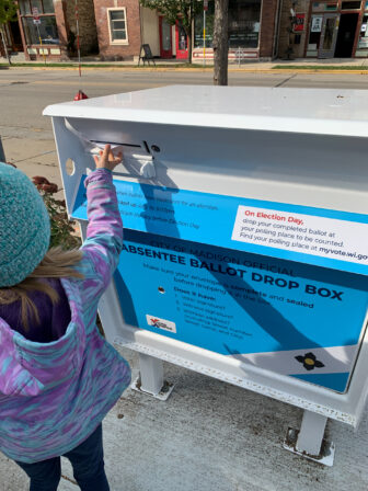 Madison resident River Horn, 6, drops the absentee ballot belonging to her father, Brad Horn, into a ballot drop box on Williamson Street in Madison, Wis., on Oct. 24, 2020. Madison is among hundreds of Wisconsin communities that have installed drop boxes to ensure absentee ballots arrive on time for Tuesday's election. Coburn Dukehart / Wisconsin Watch