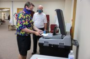 Kevin Mineau inserts his ballot into the DS200 vote-counting machine during the partisan primary in Rib Mountain, Wis., on Aug. 11, 2020. Mineau is observed by election official Mike Otten. In 2018, some servers that tabulated votes from DS200 machines in Wisconsin were left online for months, experts found, opening them up to possible hacking. Coburn Dukehart / Wisconsin Watch