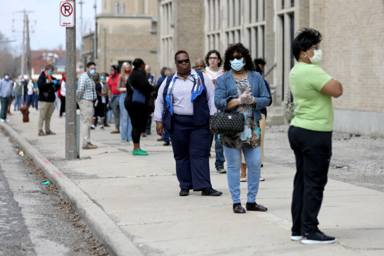 "A line of voters wraps around the block outside Washington High School in Milwaukee during the primary election on April 7, 2020. A top civil rights advocate called Wisconsin's election a ""travesty that put voters in the crosshairs of having to choose between their safety and their vote."" Various lawsuits are seeking a relaxation of Wisconsin's voting laws ahead of the Nov. 3 election due to the pandemic. Coburn Dukehart / Wisconsin Watch"