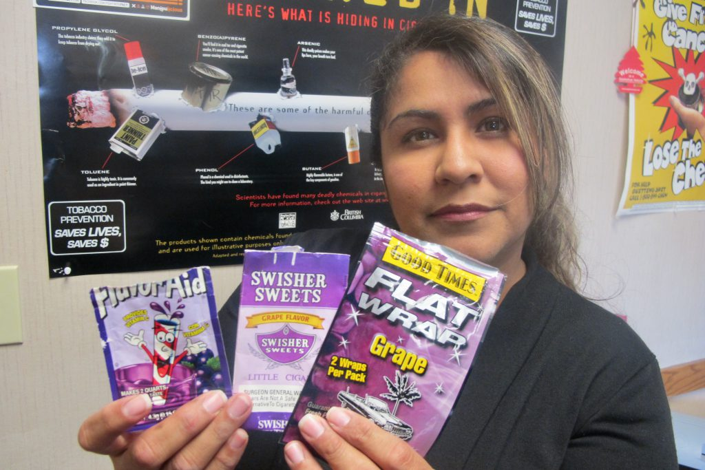 Flavored tobacco products have been blamed for hooking young people on nicotine. Here Emme Chavez, teen outreach specialist for the Wisconsin Hispanic Tobacco Prevention Network, holds packaging from one candy-flavored product (left) next to two candy-flavored tobacco wrappers in 2013. File photo by Edgar Mendez/NNS.