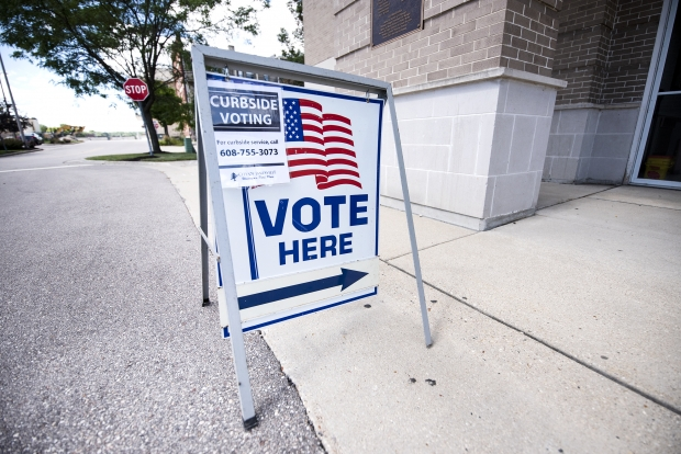 A sign at an in-person early voting location explains how to access curbside voting on Monday, July 27, 2020, in Janesville, Wis. Angela Major/WPR